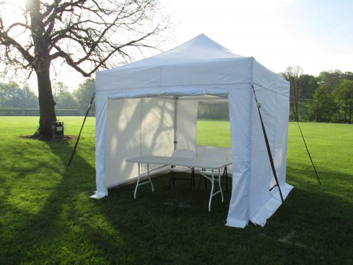 Garden party gazebo in white, 3m x 3m, set up on grass with table and two chairs.